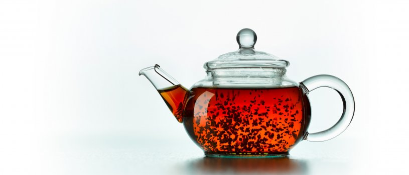Drinks photograph close up of an individual serving glass teapot filled with loose leaf tea infusing and swirling around the teapot, shot isolated on a reflective white background