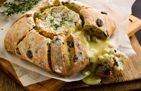 Food photograph of a baked camembert inside an olive pave, golden crusty bread studded with olives encasing a molten baked camembert which is spilling out where the bread has been torn, served on white wax paper in a rustic setting on a wooden table
