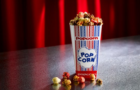 Food photograph of a cinema or comedy club portion of popcorn in a paper popcorn bag with kernels covered in various seasoning scattered around on a steel tabletop with a red curtain and spotlight in the background
