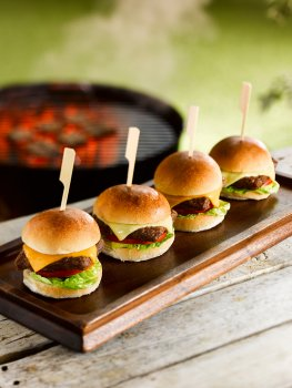 Food photograph of four miniature slider burger canapes, mini brioche buns filled with miniature burger patties, lettuce, tomato and cheese, served on skewers, shot in an outdoor setting on a picnic table in front of a lit barbecue