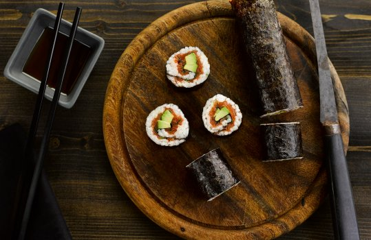 Aerial food photograph of a smoked salmon and avocado sushi roll, a whole sushi roll wrapped in nori shot on a wooden cutting board with a vintage slicing knife, with slices of the sushi roll stood on the board so show the salmon and fresh avocado filling. Shot on a dark wooden background with a dish of soy sauce and chopsticks