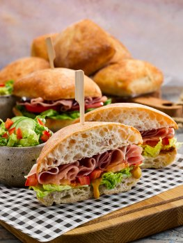 Food photograph of a ham salad sandwich, a golden sourdough sandwich roll filled with curled folded slices of cured ham, thick slices of fresh tomato, shredded lettuce and mustard. Served on parchment paper on a wooden board with bowls of lettuce salad and other sandwiches, with a second board piled high with sandwich rolls shot on a grey background