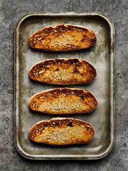 Aerial food photograph of sourdough toast, four slices of golden sourdough toast shot on a vintage baking tray, shot on a grey stone background