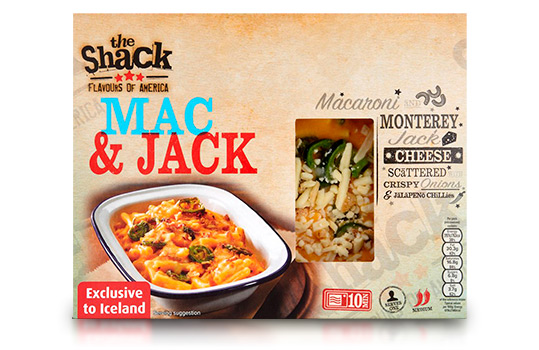 Food photograph of a front of pack image for The Shack Mac & Jack frozen ready meal, an enamel dish filled with macaroni in a thick cheese sauce topped with sliced jalapeno, shot on a dark wood setting with ingredients in the background, and the front of pack itself shown over the photograph