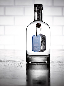 Drinks photograph of four bottles of small batch gin, each shown individually on a reflective metal tabletop with white subway tiles in the background