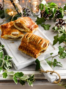 Food photograph of a festive sausage roll, crisp golden flaky pastry surrounding a sausagemeat filling shot on a painted white chopping board on a vintage white sideboard, with candles, fairy lights, ivy and pinecones