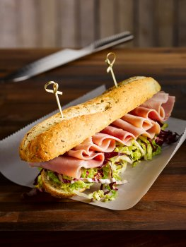 Food photograph of a ham salad baguette, a seeded baguette filled with shredded lettuce and slices of ham curled over the top. Served on baking paper on a wooden table with a chefs knife, and a white wooden wall in the background