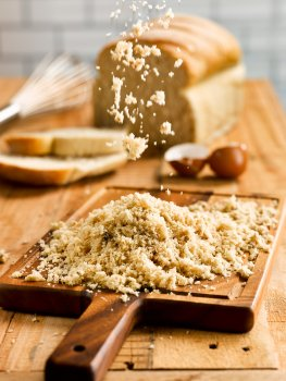 Food photograph of breadcrumbs piled on a wooden board, and being scattered. Presented on a wooden table with an old loaf of bread in the background