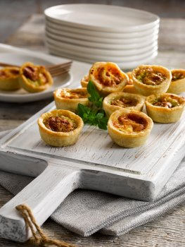 Food photograph of a selection of miniature quiches served on a white painted chopping board served with a stack of white plates on a grey wooden table