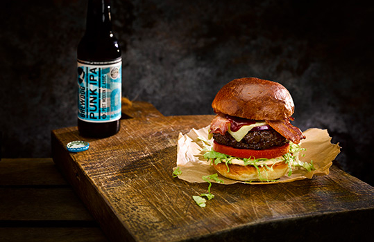 Dark moody food photograph of a homemade beef burger, a thick seared beef patty topped with melted cheese, crispy bacon and BBQ sauce, with fresh tomato and lettuce in a golden brioche bun, served on baking paper on a rustic antique chopping board with a bottle of BrewDog Punk IPA