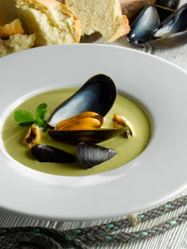 Food photograph close up of a restaurant dish, a green broccoli soup with parsley sprigs and mussels, crowned with a large mussel in its shell in the middle, shot with bread and scattered mussel shells in the background