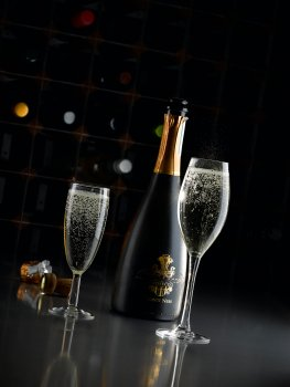 Drinks photograph of two sparkling glasses alongside an open bottle of prosecco, shot on a reflective black background in a dark set with a bottle rack in the background