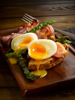 Food photograph close up of bacon, asparagus and a boiled egg, cut in half and the yolk spilling out onto the serving board, on golden slices of toast shot against a dark wood background