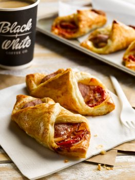 Food photograph of two crisp puff pastry turnovers filled with bacon and tomato, on a white napkin with a plastic fork, with three more turnovers and a takeaway cup of coffee in the background