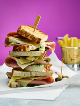 Close up food photograph of a toasted ham and cheese sandwich, thick slices of ham and melted swiss cheese between bar marked golden toasted tiger bread, served on baking paper with a basket of chips on a bright purple background
