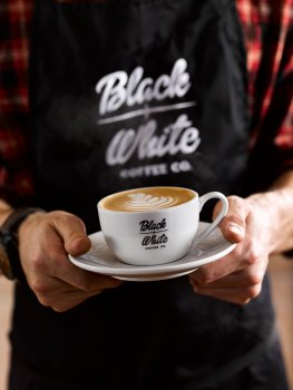 Drinks photograph of a barista in a branded apron holding a branded coffee cup and saucer, in the cup is a latte with a tulip made from the milk on the surface