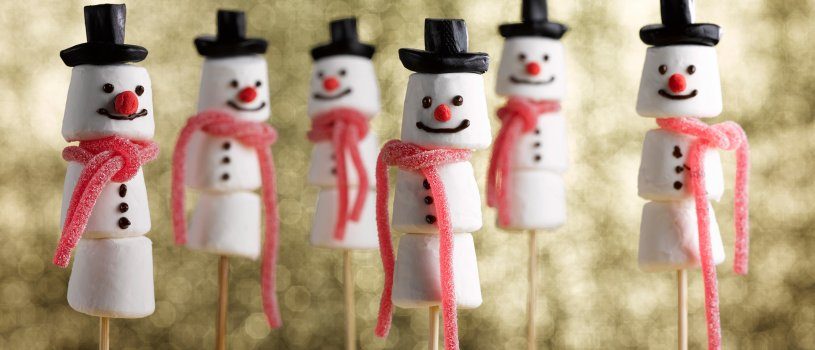 Food photograph close up of a group of marshmallow snowmen, marshmallows threaded onto skewers and decorated to look like snowmen, with liquorice hats and strawberry lace scarves, shot in a festive setting on a glittering gold background