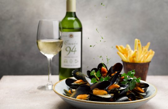 Food photograph of a bowl of steamed mussels in white wine sauce sprinkled with parsley, served on a grey background with a glass and bottle of white wine, and a portion of french fries in a copper pot