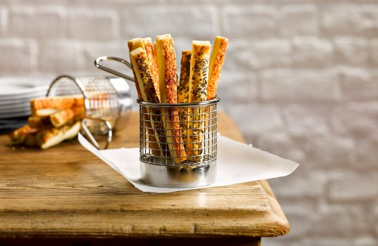 Food photograph of cheese and poppy seed breadsticks served in a steel basket on a sheet of wax paper, shot in a home style setting on a farmhouse table with white bricks in the background