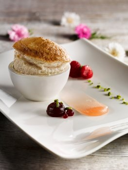 Food photograph of a fine dining dessert, a light fluffy peach souffle served with peach gel, raspberry syrup and chopped pistachios, on a light grey wooden background with flowers