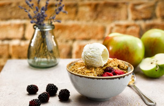 Food photograph of a golden crunchy apple and blackberry crumble served in a pale blue bowl and topped with a scoop of vanilla ice cream, the grey tabletop is decorated with scattered blackberries and large green apples in the background, along with a small glass vase of lavender