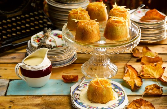 Food photograph of steamed orange puddings served with vanilla custard in a vintage milk jug, served on vintage china plates and a vintage glass cake stand - shot on a painted wooden tabletop with scattered autumn leaves, stacks of vintage plates and an antique typewriter