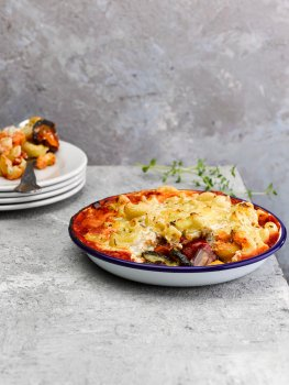 Food photograph of a vegan macaroni and Mediterranean roasted vegetable bake, an enamel dish filled with roasted aubergine, courgette, pepper and onion topped with tomato sauce and a layer of macaroni in cheese sauce. One spoonful has been removed from the dish and is served on a white plate in the background, shot on an abstract light grey setting