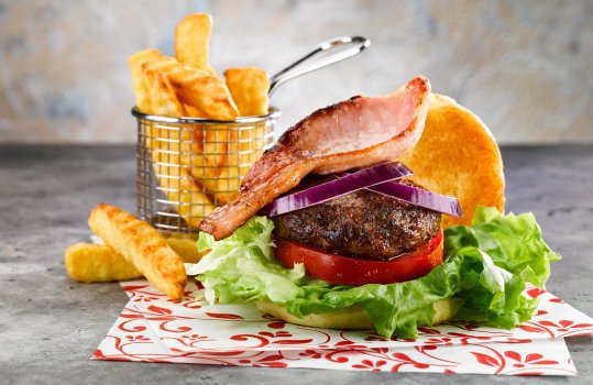 Food photograph of a homemade burger and chips, a golden toasted bun filled with large lettuce leaves, thick sliced fresh tomato, a dark crusted juicy burger patty, sliced red onion and a rasher of crispy fried bacon served on parchment paper alongside a basket of crinkle cut chips on an abstract grey background