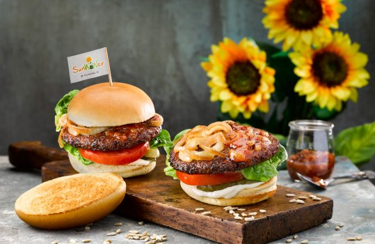 Food photograph of two SunWOWer burgers, vegan burgers made from sunflower seeds served on vegan brioche style buns with caramelised onions, thick sliced fresh tomato, lettuce, pickles and mayonnaise. Shot on a wooden board on a grey background with a glass jar of chutney and sunflowers