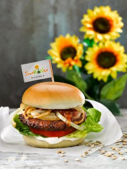 Food photograph of a SunWOWer burger, vegan burger made from sunflower seeds served on vegan brioche style buns with caramelised onions, thick sliced fresh tomato, lettuce, pickles and mayonnaise. Shot on parchment paper on a grey background with a glass jar of chutney and sunflowers