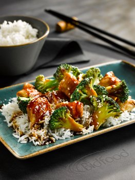 Food photograph of a chicken and broccoli stir fry, shiny glazed chunks of chicken and broccoli florets in a sweet and sour sauce, served over steamed white rice on a teal plate, with a bowl of rice and chopsticks in the background, served on a leather mat on a grey tabletop