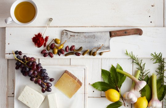 Aerial food photograph of the ingredients to make Spanish coca bread shot on painted white wooden planks, featuring feta, manchego and goats cheeses with grapes, olives, pickles, capters, fresh lemon, fresh bay and rosemary leaves, and fresh garlic bulbs