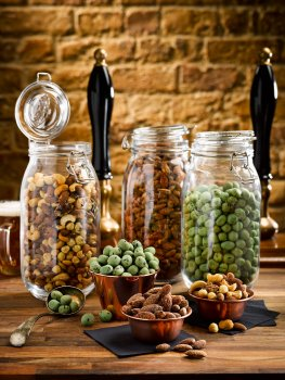 Food photograph of various bar snacks, mixed nuts, wasabi peas and smoked almonds, in large kilner jars with portions in copper ramekins; on a wooden tabletop with a brick wall, a glass of beer and beer pumps in the background