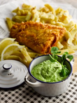 Food photograph close up of a cast iron pot filled with posh mushy peas garnished with watercress, in the background is a portion of golden battered cod and chips with lemon wedges served on newspaper