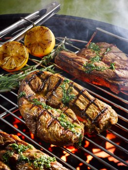 Food photograph close up of barbecued bar marked lamb leg steaks, topped with pesto sauce and shot alongside grilled lemons, on the grill of a lit barbecue in an outdoor setting