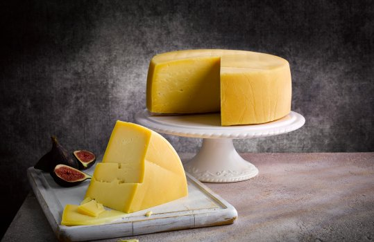 Food photograph of a whole Welsh PGI traditional Caerphilly cheese, the whole wheel is presented on a white ceramic cake stand with a wedge cut out and shown in the foreground on a white wooden board, shot against a dark background