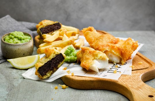 Food photograph of fish and chips, a crispy battered flakey cod fillet alongside homemade french fries, and a slice of crispy battered black pudding, served on a wooden board alongside mushy peas on a grey tabletop with a grey wall in the background