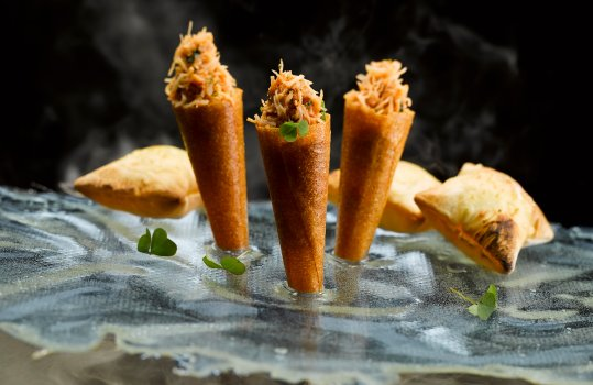 Food photograph of crab cones, a fine dining starter, brick pastry cones filled with picked crab, served stuck in an isomalt sheet on a black background with clouds of smoke
