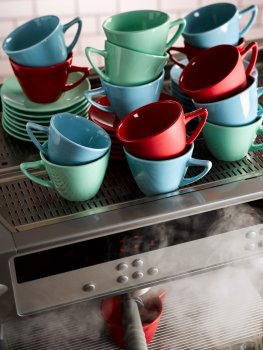 Food photograph of the making of a cup of coffee, stacks of multicoloured coffee cups on top of a commercial coffee machine, one cup in the machine being poured into, with clouds of steam billowing out from the coffee machine