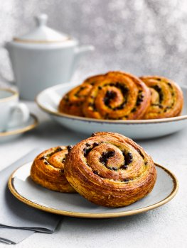 Food photograph close up of danish pastry swirls, two pastries stacked up on a plate with a platter of the same pastries, a teapot and cup and saucer in the background, with a shimmering flittered white background