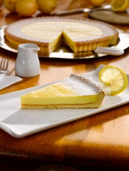 Food photograph of a slice of lemon tart on a rectangular white plate, dusted with icing sugar and garnished with a slice of lemon, with the whole tart with a slice taken out in the background, along with a selection of lemons